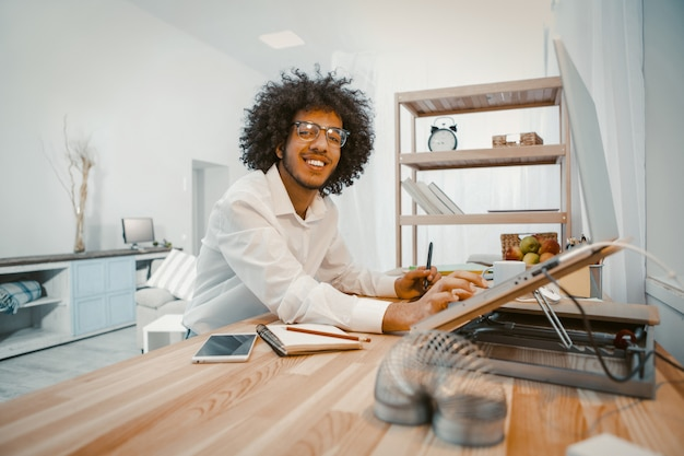 Glücklicher junger mann, der mit laptop zu hause am arbeitsplatz arbeitet