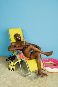 Glücklicher junger mann, der mit strandring als donut auf blauem studiohintergrund ruht und lächelt. konzept der menschlichen gefühle, des gesichtsausdrucks, der sommerferien oder des wochenendes. chill, sommerzeit, meer, meer.