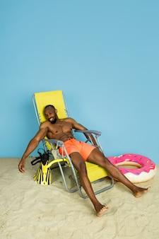 Glücklicher junger mann, der mit strandring als donut auf blauem studiohintergrund ruht und schläft. konzept der menschlichen gefühle, gesichtsausdruck, sommerferien oder wochenende. chill, sommer, meer, meer.