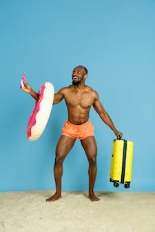 Glücklicher junger mann, der mit strandring als donut und tasche auf blauem raum ruht