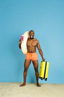 Glücklicher junger mann, der mit strandring als donut und tasche auf blauem studiohintergrund ruht. konzept der menschlichen gefühle, des gesichtsausdrucks, der sommerferien oder des wochenendes. chill, sommerzeit, meer, meer.