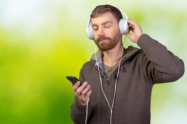 Glücklicher junger mann, der musik mit kopfhörern hört
