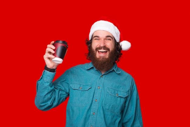 Glücklicher junger mann, der papierkaffeetasse über rotem hintergrund hält