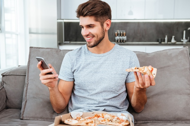 Glücklicher junger mann, der plaudert und pizza isst, während er auf sofa sitzt.