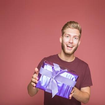 Glücklicher junger mann, der purpurrote geschenkbox mit bogen hält