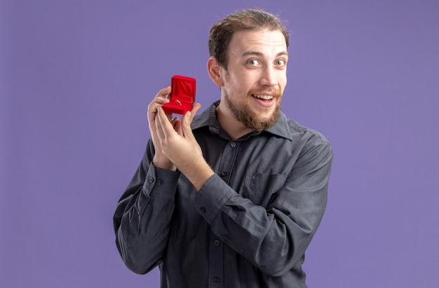 Glücklicher junger mann, der rote box mit verlobungsring hält und kamera betrachtet, die fröhlich valentinstagkonzept steht, das über lila wand steht