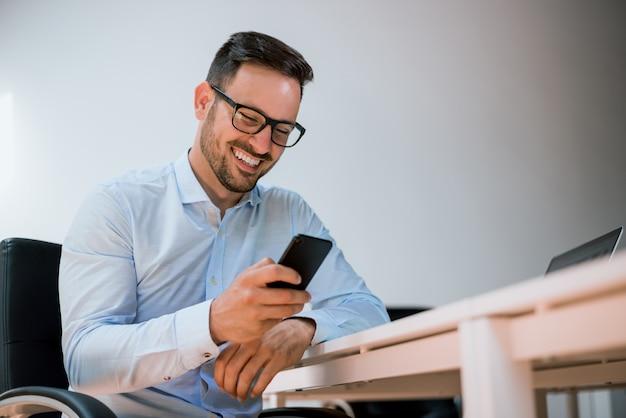 Glücklicher junger mann, der sein intelligentes telefon im büro verwendet