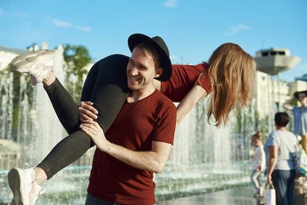 Glücklicher junger mann, der seine freundin auf einer schulter im freien hält
