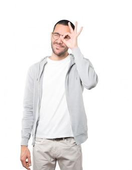 Glücklicher junger mann, der seine hände wie ein fernglas benutzt