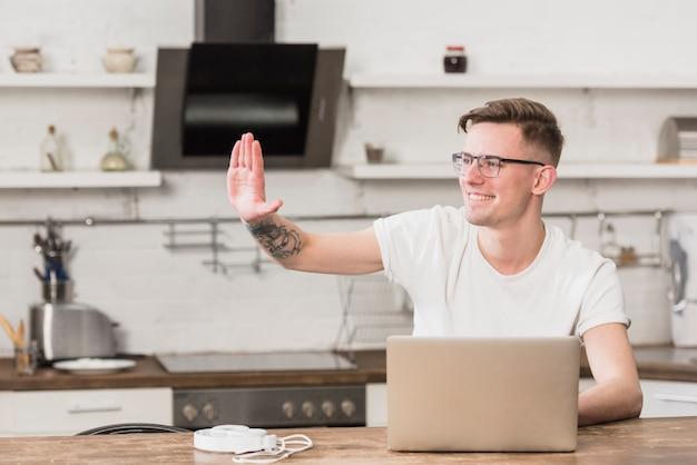Glücklicher junger mann, der seine hand mit laptop auf tabelle in der küche wellenartig bewegt