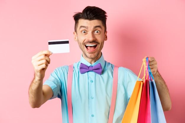 Glücklicher junger mann, der seine kreditkarte gibt und einkaufstaschen hält, mit rabatten kauft, auf rosa steht und lächelt.
