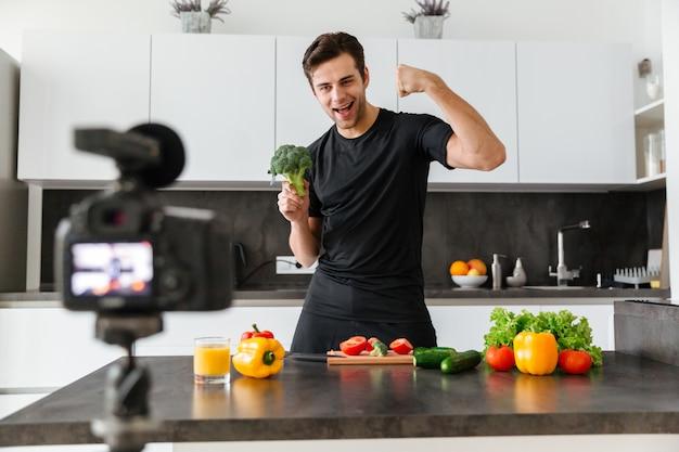 Glücklicher junger mann, der seine videoblogepisode filmt