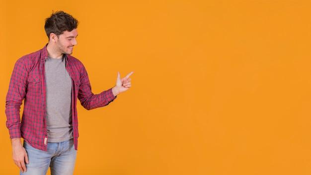 Glücklicher junger mann, der seinen finger gegen einen orange hintergrund zeigt
