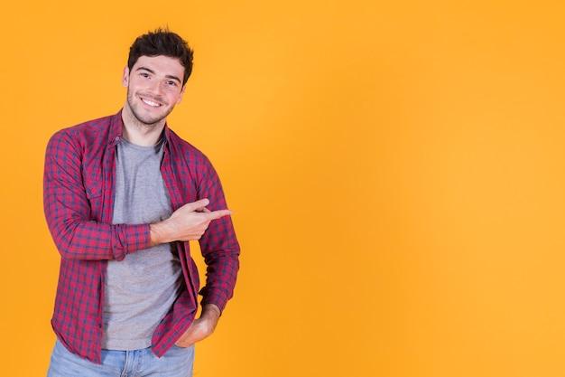 Glücklicher junger mann, der seinen finger gegen gelben hintergrund zeigt