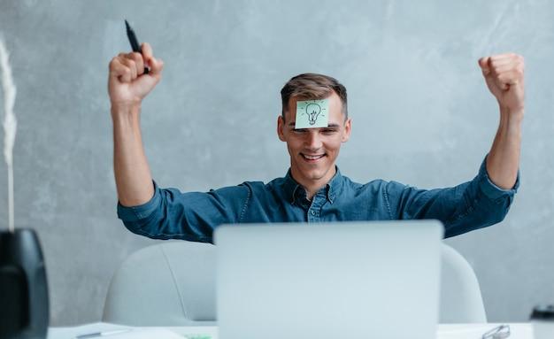 Glücklicher junger mann, der seinen laptopbildschirm betrachtet