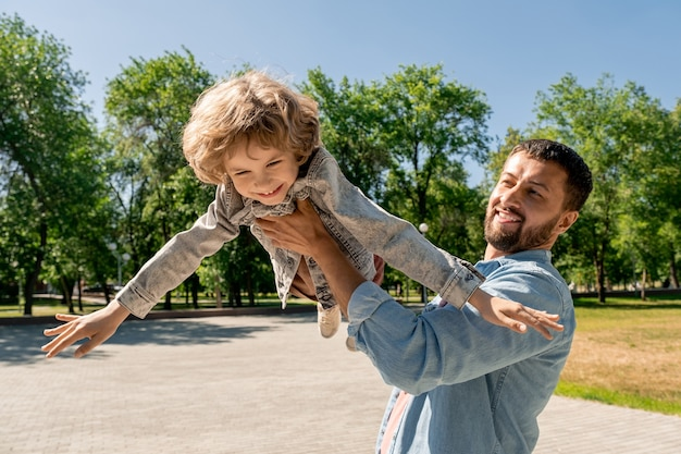 Glücklicher junger mann, der seinen niedlichen fröhlichen kleinen sohn hält, ihn anhebt und wirbelt, während er spaß hat und zeit im park an sonnigem tag genießt