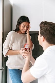 Glücklicher junger mann, der seiner freundin einen vorschlag mit einem ring in einer schachtel zu hause macht
