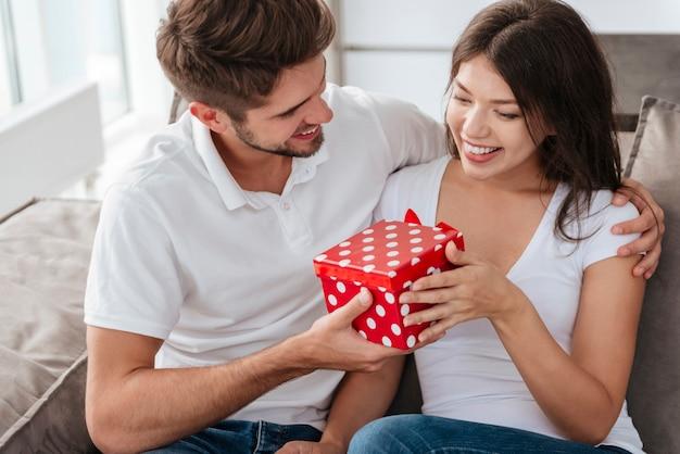 Glücklicher junger mann, der seiner schönen freundin zu hause ein geschenk gibt