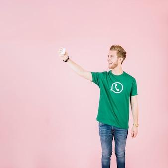 Glücklicher junger mann, der selfie mit smartphone nimmt