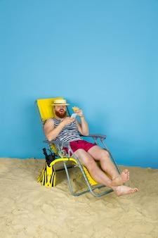 Glücklicher junger mann, der sich ausruht, nimmt selfie und trinkt cocktails auf blauem studiohintergrund. konzept der menschlichen gefühle, des gesichtsausdrucks, der sommerferien oder des wochenendes. chill, sommer, meer, meer, alkohol.