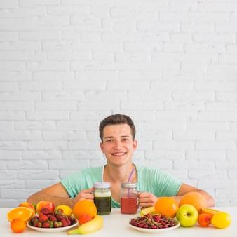 Glücklicher junger mann, der smoothies mit bunten frischen organischen früchten auf schreibtisch hält