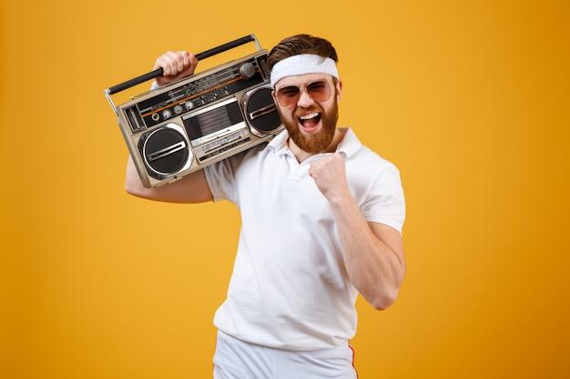 Glücklicher junger mann, der sonnenbrille hält, die tonbandgerät hält