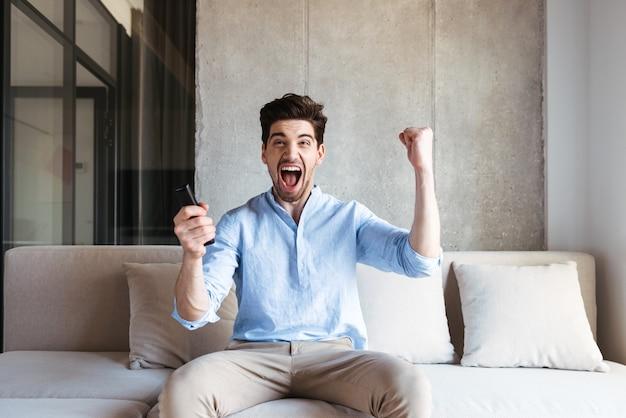Glücklicher junger mann, der tv-fernbedienung hält