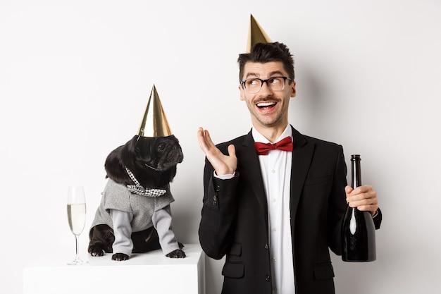 Glücklicher junger mann, der urlaub mit süßem hund feiert, champagner hält und lächelt, mops und besitzer tragen partykostüme, weißer hintergrund.