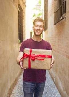 Glücklicher junger mann, der valentinsgrußgeschenk hält
