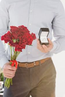 Glücklicher junger mann, der verlobungsring- und blumenblumenstrauß hält