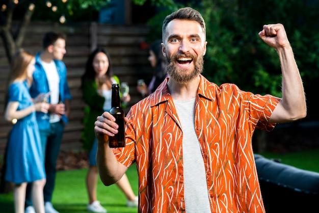 Glücklicher junger mann der vorderansicht, der bier hält