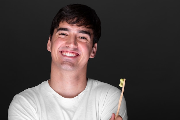 Glücklicher junger mann, der zahnbürste hält