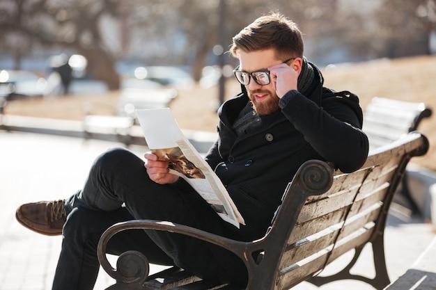 Glücklicher junger mann, der zeitung auf bank in der stadt liest