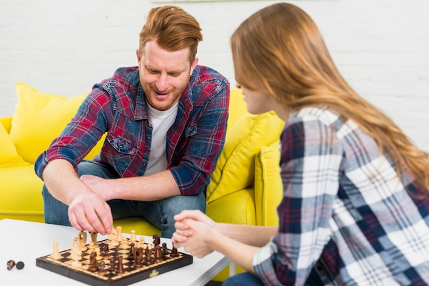 Glücklicher junger mann, der zu hause das schach mit ihrer freundin spielt
