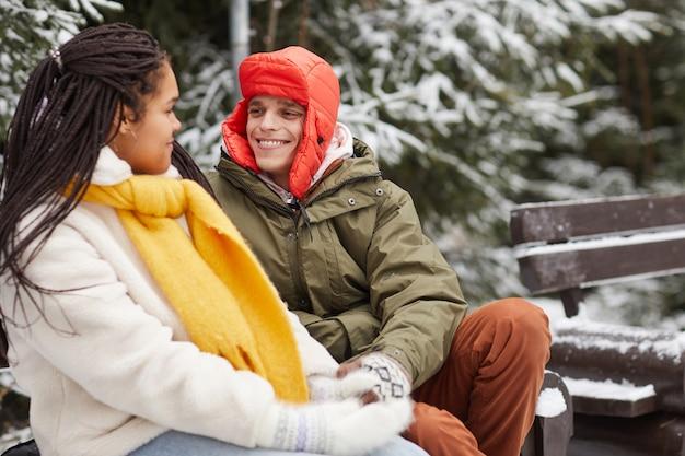 Glücklicher junger mann, der zur frau während ihres gesprächs auf der bank im winterpark lächelt