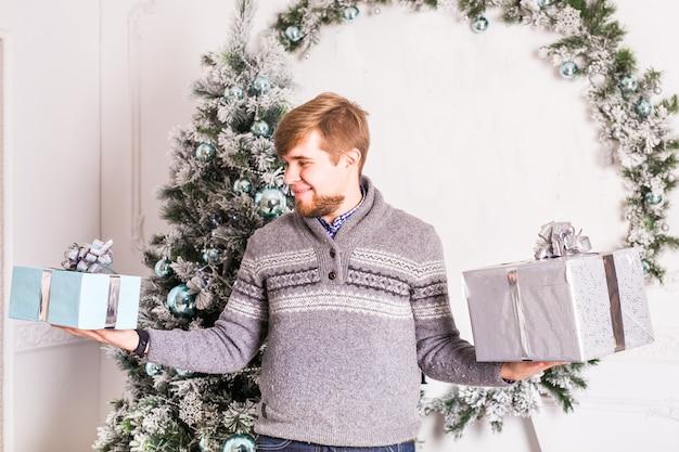 Glücklicher junger mann, der zwei geschenkboxen auf weihnachtsbaumhintergrund hält.