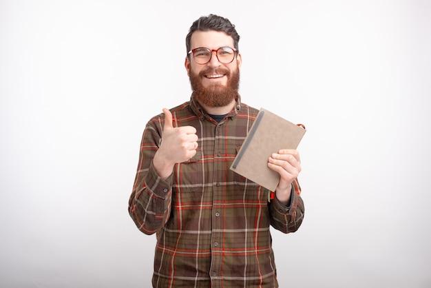 Glücklicher junger mann hält ein notizbuch oder ein buch, lächelt in die kamera und zeigt wie knopf oder daumen oben auf leerraum.