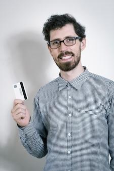 Glücklicher junger mann hält eine kreditkarte in seiner hand