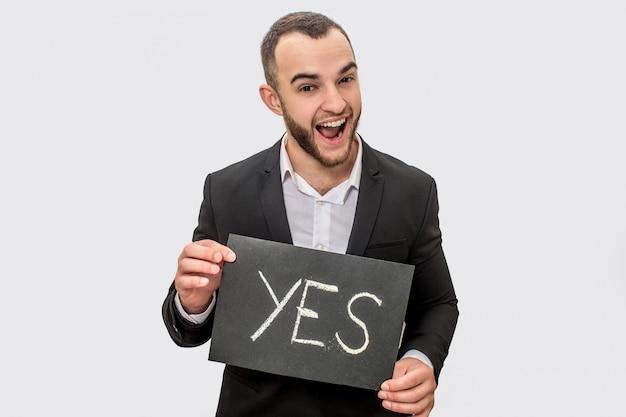 Glücklicher junger mann im anzug steht nd hält tablette mit geschriebenem wort ja. guy schaut direkt vor die kamera. er trägt einen anzug.