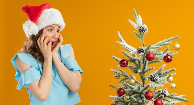 Glücklicher junger mann im blauen oberteil und im weihnachtsmannhut, der gelbe brille trägt