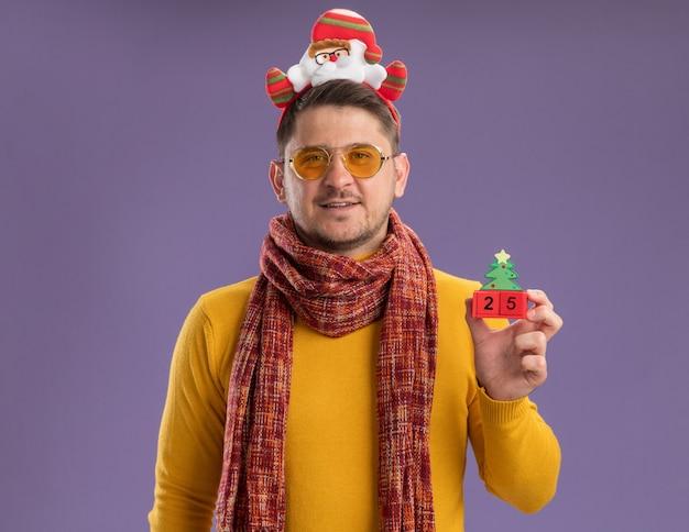 Glücklicher junger mann im gelben rollkragenpullover mit warmem schal und brille, die lustigen rand mit weihnachtsmann auf kopf trägt, der spielzeugwürfel mit nummer fünfundzwanzig steht, die über lila wand stehen