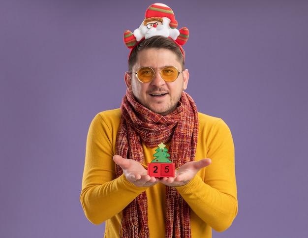 Glücklicher junger mann im gelben rollkragenpullover mit warmem schal und brille, die lustigen rand mit weihnachtsmann auf kopf tragen spielzeugspielwürfel mit nummer fünfundzwanzig stehen über lila hintergrund tragen