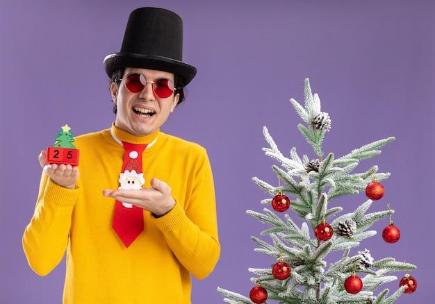 Glücklicher junger mann im gelben rollkragenpullover und in den gläsern, die schwarzen hut und lustige krawatte halten, die würfel mit der nummer fünfundzwanzig halten, die mit dem arm der hand lächelnd neben einem weihnachtsbaum stehen