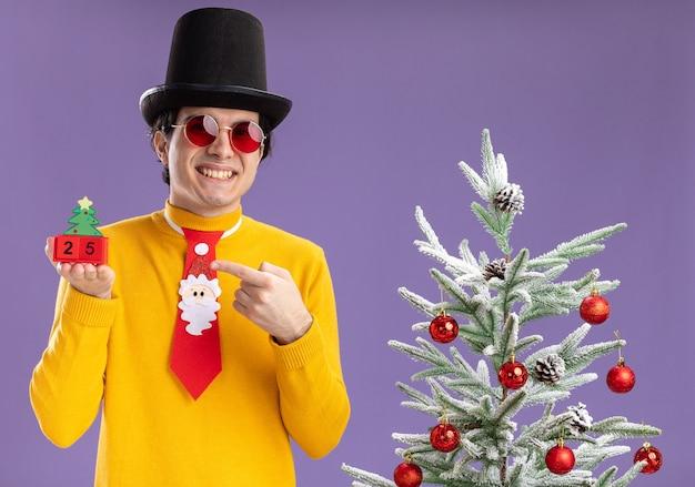 Glücklicher junger mann im gelben rollkragenpullover und in der brille, die schwarzen hut und lustige krawatte tragen, die würfel mit der nummer fünfundzwanzig zeigen