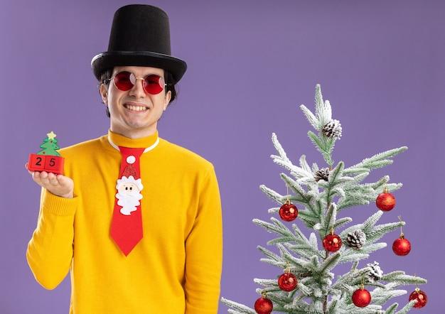 Glücklicher junger mann im gelben rollkragenpullover und in der brille, die schwarzen hut und lustige krawatte tragen würfel mit nummer fünfundzwanzig tragen