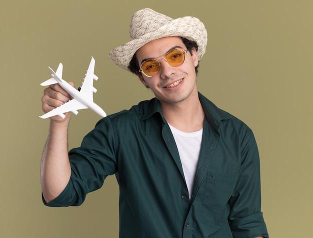 Glücklicher junger mann im grünen hemd und im sommerhut, der brillen hält, die spielzeugflugzeug halten, das vorne mit lächeln auf gesicht über grüner wand steht