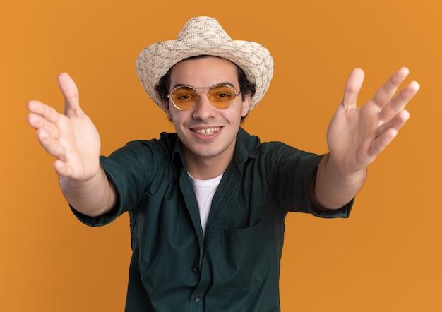 Glücklicher junger mann im grünen hemd und im sommerhut, der die brille trägt, die vorne mit lächeln auf gesicht steht, das über orange wand steht