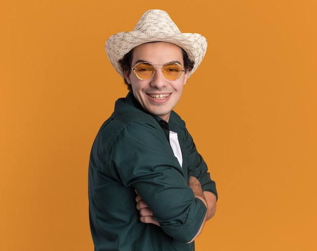 Glücklicher junger mann im grünen hemd und im sommerhut, die brille tragen, die vorne mit lächeln auf gesicht steht, das über orange wand steht