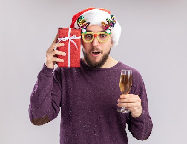 Glücklicher junger mann im lila pullover und in der weihnachtsmannmütze, die lustige gläser tragen, die glas champagner halten und das lächelnde fröhliche neujahrsferienkonzept präsentieren, das auf weißer wand steht