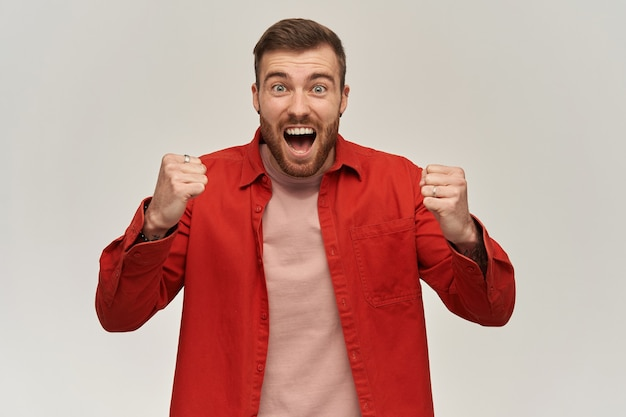 Glücklicher junger mann im roten hemd mit bart und umklammerten fäusten, die vorne schauen und über weiße wand schreien erfolgs- und feier-siegeskonzept